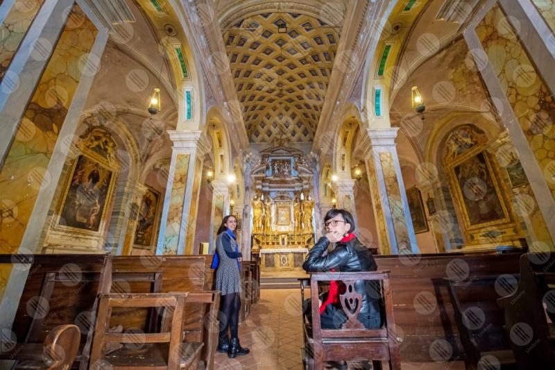 Collegiata di San Michele Arcangelo interno colonne volte altare affreschi colori arte donne ragazze panche  Panicale