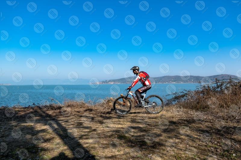 Lago Trasimento bici ciclista San Feliciano sponda acqua cielo cielo sereno uomo panorama vista paesaggio  Trasimeno