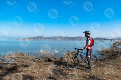 trasimeno Trasimeno lake bike bicycle cyclist San Feliciano shore swans water sky clear sky man panorama view landscape