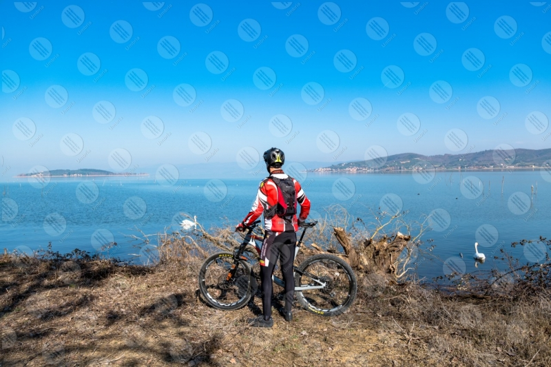 Lago Trasimento bici ciclista San Feliciano Isola Polvese sponda cigni acqua cielo cielo sereno uomo panorama vista paesaggio  Trasimeno