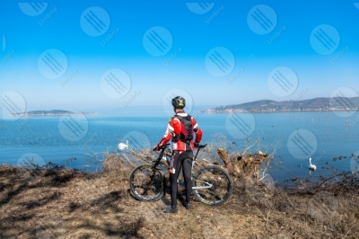 trasimeno Trasimeno lake bike bicycle cyclist San Feliciano Polvese Island shore swans water sky clear sky man panorama view landscape