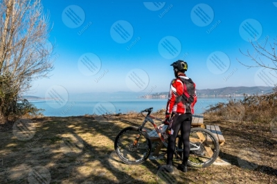 trasimeno Trasimeno lake bike bicycle cyclist San Feliciano Polvese Island shore water sky clear sky man panorama view landscape