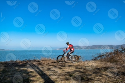 trasimeno Trasimeno lake bike bicycle cyclist San Feliciano Polvese Island shore water sky clear sky panorama view landscape man