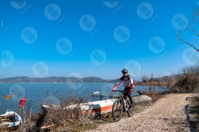 trasimeno Trasimeno lake bike bicycle cyclist shore boats water pathway sky clear sky panorama view landscape man swans