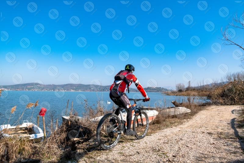 Trasimeno lake bike bicycle cyclist shore boats water pathway sky clear sky panorama view landscape man swans  Trasimeno