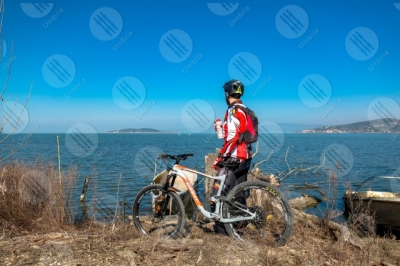 trasimeno Trasimeno Lake bike bicycle cyclist San Feliciano Polvese Island shore boats water sky clear sky panorama view landscape man