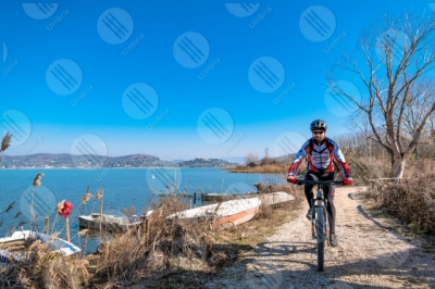 trasimeno Trasimeno Lake bike bicycle cyclist shore pathway boats water sky clear sky panorama view landscape man