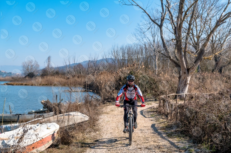Trasimeno Lake bike bicycle cyclist shore pathway boats water sky clear sky panorama view landscape man  Trasimeno