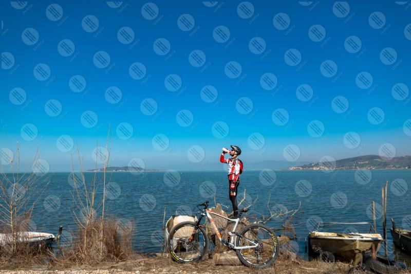 Lago Trasimeno bici ciclista San Feliciano Isola Polvese sponda acqua barche cielo cielo sereno panorama vista paesaggio uomo  Trasimeno