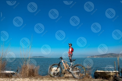 trasimeno Trasimeno Lake bike bicycle cyclist San Feliciano Polvese Island shore water boats sky clear sky panorama view landscape man