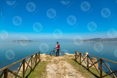 trasimeno Trasimeno Lake bike bicycle cyclist San Feliciano Polvese Island shore pathway water sky clear sky panorama view landscape man
