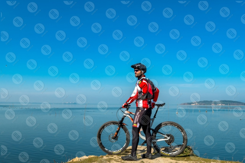 Trasimeno Lake bike bicycle cyclist Polvese Island shore pathway water sky clear sky panorama view landscape man  Trasimeno